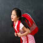 Criança com mochila pesada