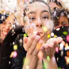 Mulher assopra confete em carnaval