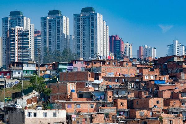 Faceta visível da segregação espacial entre ricos e pobres: Favela de Paraisópolis circundada por condomínios luxuosos, São Paulo.