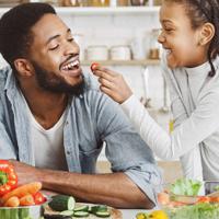 Pai e filha comendo vegetais