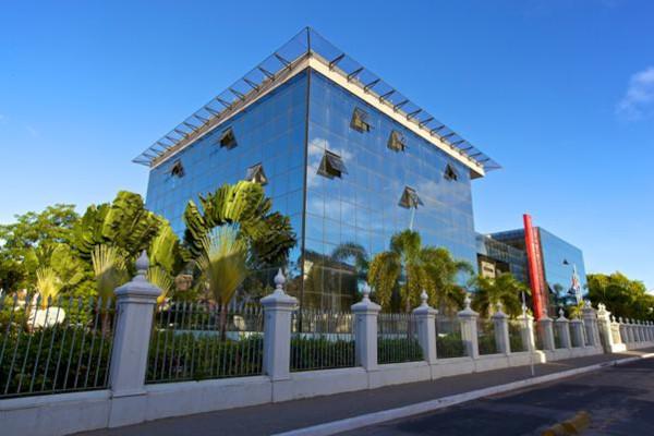 Foto do palácio da República dos Palmares, edifício espelhado com árvores ao seu redor e protegido por um muro.