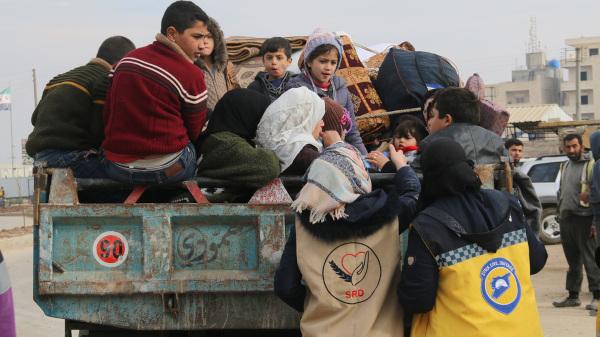 Voluntárias de grupos pacificadores distribuem medicamentos a crianças refugiadas sírias em caminhão.[1]