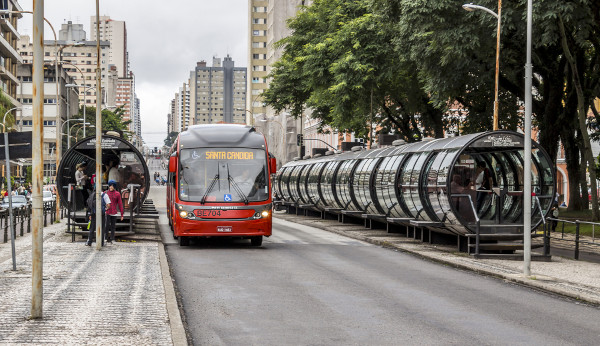 Foto de um ônibus de Curitiba recebendo passageiros.