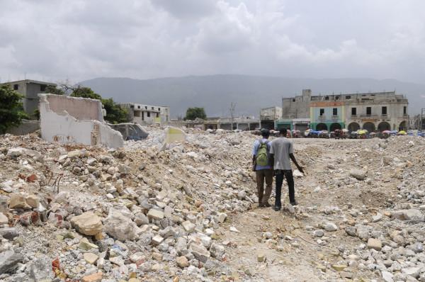 Pessoas caminham sobre os escombros de edifícios destruídos pelo terremoto que acometeu o Haiti em 2010.[1]