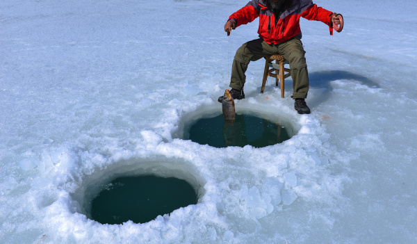 Homem pescando em ambiente congelado.