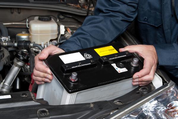 Bateria automotiva sendo instalada.