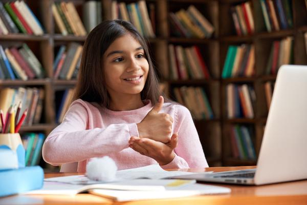 Foto de criança conversando em língua de sinais em frente a um computador.
