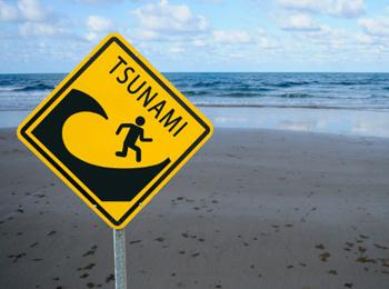 placa de aviso de risco de tsunami em praia