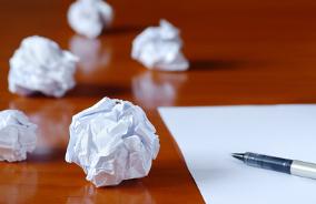 Cinco papéis amassados em cima de uma mesa com folha em branco e caneta