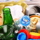 Garrafas, tampinhas e latas de alumínios em lixeira