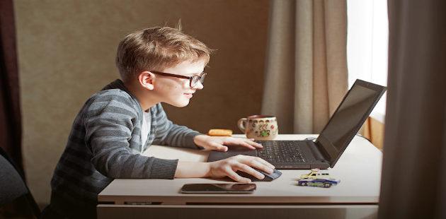 Menino assiste filme no notebook
