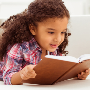 Menina lendo livro deitada