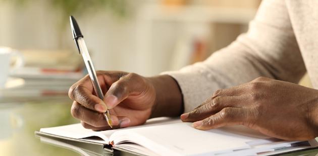 Close de mão escrevendo em caderno