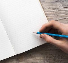 Mulher segurando caneta apoiada em caderno sob mesa