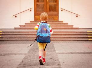 Criança com mochila nas costas entrando na escola