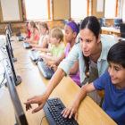 Professora orientando aluno em frente ao computador
