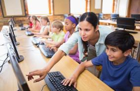 Alunos e professor mexem no computador