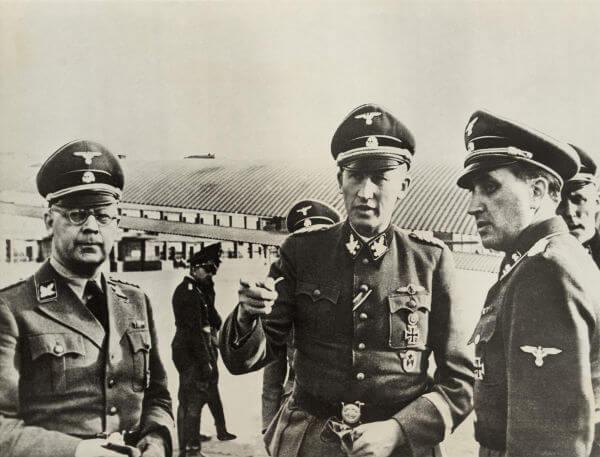 Na imagem estão Heinrich Himmler (à esquerda) e Reinhard Heydrich (no centro), os dois arquitetos da Solução Final.*