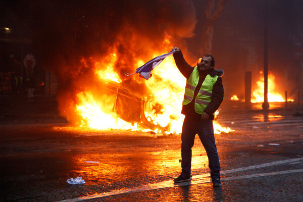 Manifestantes queimando carro durante protesto. A discordância é marca fundamental da democracia.