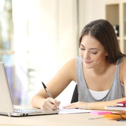 Adolescente escrevendo com notebook e livros ao redor