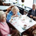 Idosos tomando café e jogando damas em cima da mesa