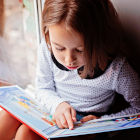 Menina lendo livro infantil