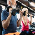 Dois idosos levantando peso na academia