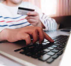 Pessoa utilizando o notebook com cartão de crédito na mão