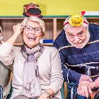 Homem e mulher idosos se divertindo vestidos com objetos coloridos