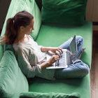 Mulher sentada em sofá usando um notebook sobre o colo